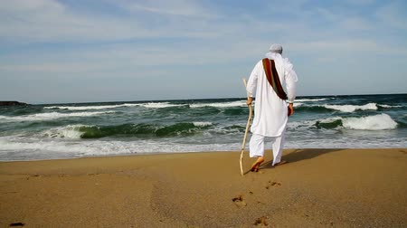 egyiptom : Middle Eastern Man with Staff Walking toward Sea Religious Concept HD