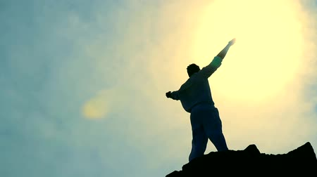 osoba : Worship Pose Colorful Silhouette of Man on Mountain Peak Raising Arms at Sun Wideo