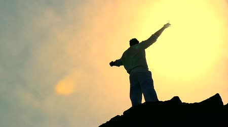 felicidade : Mans Sylohuette Stretching Arms toward Heaven Colorful Religious Background HD Stock Footage