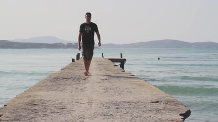 idil : A man goes on the concrete pier in the sunrise Stok Video