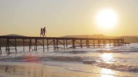 aydınlatmalı : Young Couple silhouette Wwalking on Pier Romantic Concept HD Stok Video