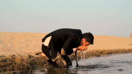 perdido : Dirty Tired Exhauseted Man in Suit Reaching Water in Desert Salvation HD
