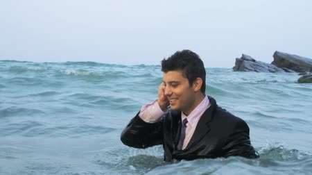 adam : Business man calling cell phone in the sea HD