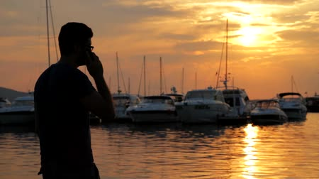 powerful : Young Man Talking on Phone at Sunset Sea Boats HD