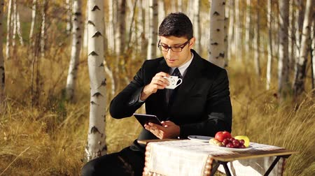 emocje : Young man reading tablet during breakfast outdoors Business Wideo