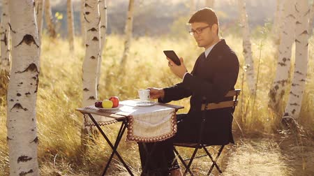 ormanda yaşayan : Businessman Using tablet outdoors breakfast in nature concept Stok Video