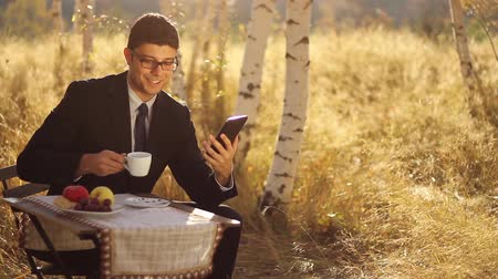 munkahelyek : Young businessman using tablet pc having breakfast outdoors Stock mozgókép