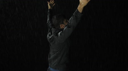 demanda : Young Man Raising in Pouring Rain Redemption Concept Religion