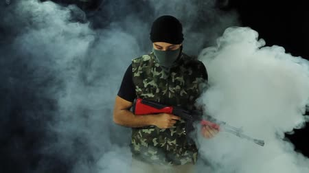 терроризм : Criminal Masked Gunman Armed Terrorist Walking Out Smoke Grenade