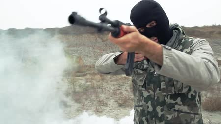 autoridade : Masked Man With Kalashnikov Walking Through Smoke War Field