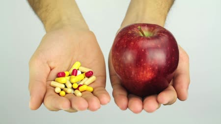 medicamento : Hands offering Choice Apple or Pills
