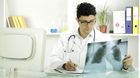 healthy office : Young Doctor Examining Xray Writing Down Results Diagnosis Stock Footage