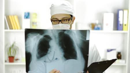 dokumentum : Portrait Doctor White Mask Looking Xray Writing Down Diagnosis