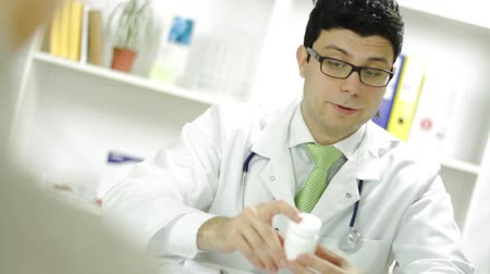 médicos : Medical Doctor Checking Patient Records and Offering Pills