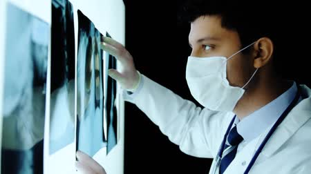 sebész : Handsome Young Surgeon Examining Scans Close Up