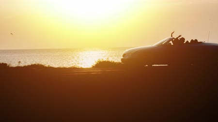 luksus : Silhouette Of Convertible Cabriolet Car Driving On Seaside At Sunset Couple On Vacation Sunset Travel Holiday Trip Love Adventure Sunshine Golden Hour Drone Tracking Shot