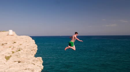 Young Man Jumping Off Cliff Into The Ocean Summer Vacation Extreme Rock Jumping Diving Concept Стоковые видеозаписи