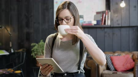 Young Beautiful Successful Woman Working On Her iPad In A Coffee Shop Drinking Coffee In Slow Motion Female Success Concept 4K Shot