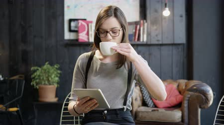 Pretty Girl Drinking Coffee In A Coffee Shop Looking At Her Tablet Smiling Working Online Startup Concept Happiness Independence Own Business Slow Motion