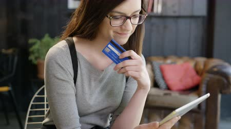Pretty Young Woman Picking Up Credit Card Wondering Whether To Purchase Something Online Looking At Tablet In A Cafe Online Shopping Choice Concept Slow Motion Shot Stock mozgókép