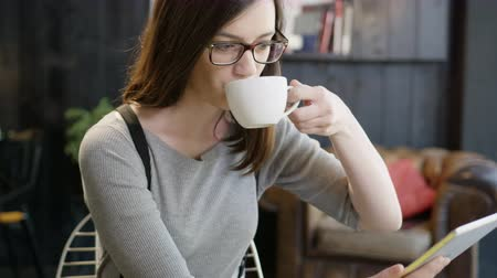 Beautiful Trendy Young Woman With Glasses Sitting At A Cafe Drinking Espresso Coffee And Looking At An tablet Smiling And Reading Slow Motion Shot Стоковые видеозаписи
