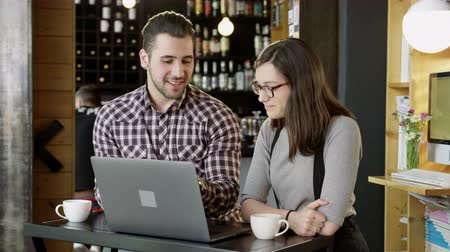 Young Couple Discussing And Laughing Looking At Laptop Computer Drinking Coffee At Coffee House Slow Motion Shot Dostupné videozáznamy