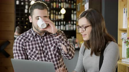 Man And Woman Discussing Project Looking At Laptop At Coffee House Smiling Teamwork Online Business Concept Slow Motion Shot Стоковые видеозаписи
