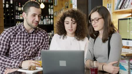 Young Woman Leader Manager Explaining Project To Her Team Looking At A Laptop Teamwork Meeting At A Coffee Bar Slow Motion Shot