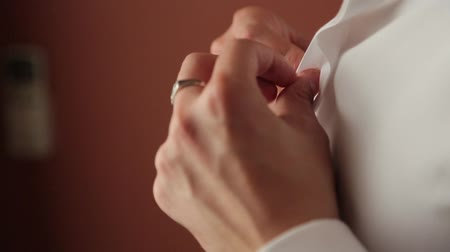 clothing : Man buttoning a white shirt.