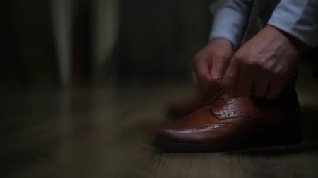 носить : Man tying the laces on the brown shoes, oxfords. Стоковые видеозаписи