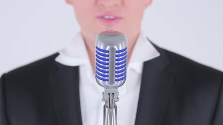 талант : Man singing into  a microphone on a white background. Стоковые видеозаписи