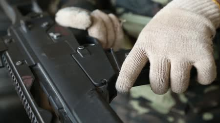 bulletproof : Man wearing gloves reloads his weapon.