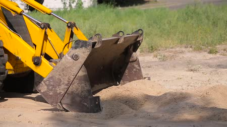 yükleyici : Yellow bulldozer rows sand in the bucket.