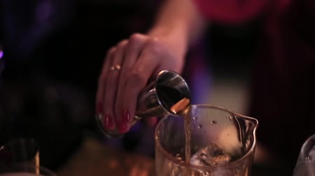 смешивание : Girl bartender pours the liquor into a glass with ice.