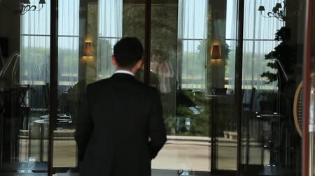 entrance : Businessman in a black suit enters the business center. Stock Footage