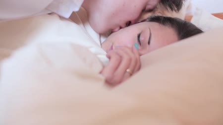 casal heterossexual : Man kisses a sleeping girl and she wakes up.
