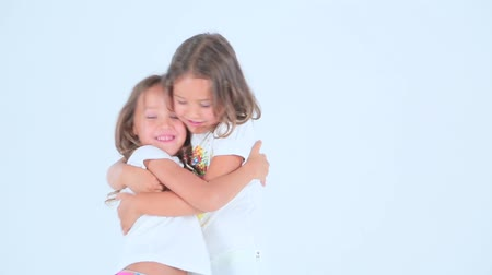 объятие : Little girls hugging and laughing on the white background. Стоковые видеозаписи