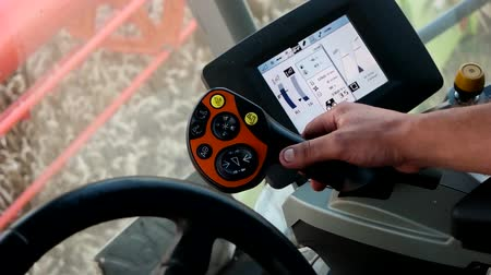 Man manages harvester combine harvester with a control panel.