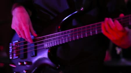 черные волосы : A man plays an electric guitar at a concert.