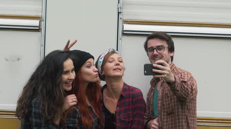 fotografando : Friends do selfie near the travel trailer.