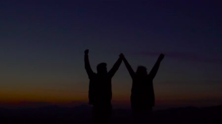 double happiness : Silhouette of couple on the background of mountains.
