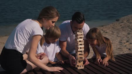 ga : Happy family have fun playing jenga game.