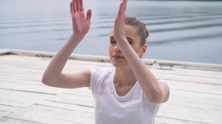 sakk : girl practicing yoga near the river. Stock mozgókép