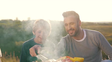 father and son fry sausages on grill. Stock Footage