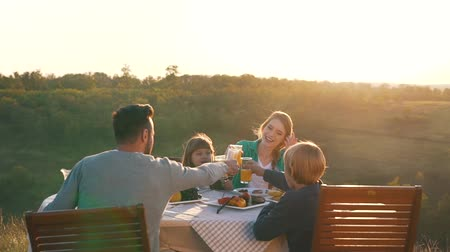 ailelerin : Happy family have dinner in beautiful countryside.