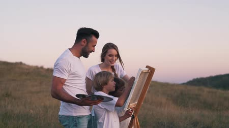 Happy family draw picture in the field. Stock Footage