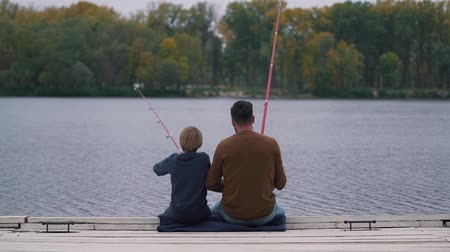 Father and son fish on the lake. Stock Footage