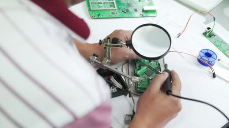 soldering iron : Engineer solder a chipset under a magnifying glass. Stock Footage