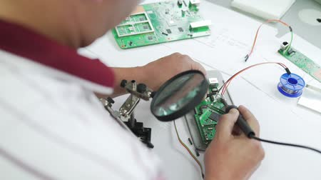 electrico : Ingeniero soldar un conjunto de chips de primer plano. Archivo de Video