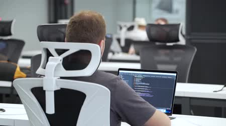 Programmer works on laptop in the office. Stock mozgókép